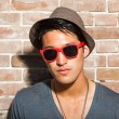 Royalty-Free Stock Photo: Urban asian man with red sunglasses. Good looking. Cool guy. Wearing grey shirt and hat. Standing in front of brick wall.