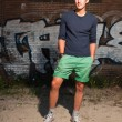 Urban asian man. Good looking. Cool guy. Wearing dark blue shirt and green shorts. Standing in front of brick wall with graffiti. — Stock Photo