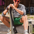 Urban asian man with red sunglasses and skateboard sitting on street. Good looking. Cool guy. Wearing blue white striped sweater and green shorts. Old neglected building in the background. — Stock Photo #11950107