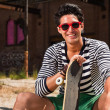 Urban asian man with red sunglasses and skateboard sitting on street. Good looking. Cool guy. Wearing blue white striped sweater and green shorts. Old neglected building in the background. — Stock Photo #11950123