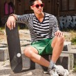 Urban asian man with red sunglasses and skateboard sitting on street. Good looking. Cool guy. Wearing blue white striped sweater and green shorts. Old neglected building in the background. — Stock Photo #11950128
