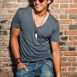 Urban asian man with red sunglasses. Good looking. Cool guy. Wearing grey shirt and hat and jeans. Standing in front of brick wall. — Stock Photo
