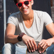 Urban asian man with red sunglasses and skateboard sitting on stairs. Good looking. Cool guy. Wearing grey shirt and jeans. — Stock Photo #11950140