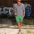 Urban asian man with red sunglasses. Good looking. Cool guy. Wearing blue white striped sweater and green shorts. Standing in front of wall with graffiti. — Stock Photo #11950145