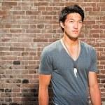 urbano uomo asiatico. Attraente. ragazzo cool. indossa camicia grigia. in piedi davanti al muro di mattoni — Foto Stock
