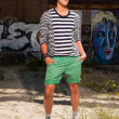 Royalty-Free Stock Photo: Urban asian man with red sunglasses. Good looking. Cool guy. Wearing blue white striped sweater and green shorts. Standing in front of wall with graffiti.