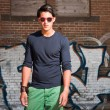Urban asian man with red sunglasses. Good looking. Cool guy. Wearing dark blue shirt and green shorts. Standing in front of brick wall with graffiti. — Stock Photo