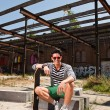 Urban asian man with red sunglasses and skateboard sitting on street. Good looking. Cool guy. Wearing blue white striped sweater and green shorts. Old neglected building in the background. — Stock Photo #11950217