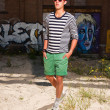 Urban asian man with red sunglasses. Good looking. Cool guy. Wearing blue white striped sweater and green shorts. Standing in front of wall with graffiti. — Stock Photo