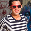Urban asian man with red sunglasses. Good looking. Cool guy. Wearing blue white striped sweater. Standing in front of wooden wall with graffiti. — Stock Photo