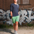 Stock Photo: Urban asian man with red sunglasses. Good looking. Cool guy. Wearing dark blue shirt and green shorts. Standing in front of brick wall with graffiti.