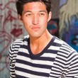 Urban asian man. Good looking. Cool guy. Wearing blue white striped sweater. Standing in front of wooden wall with graffiti. — Stock Photo