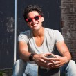 Urban asian man with red sunglasses and skateboard sitting on stairs. Good looking. Cool guy. Wearing grey shirt and jeans. Old neglected building in the background. — Stock Photo