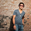 Urbasimwith red sunglasses. Good looking. Cool guy. Wearing grey shirt and hat and jeans. Standing in front of brick wall. — Stock Photo #11950260
