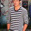 Urban asian man. Good looking. Cool guy. Wearing blue white striped sweater and green shorts. Standing in front of wooden wall with graffiti. — Stock Photo #11950264