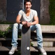 Urban asian man with skateboard sitting on stairs. Good looking. Cool guy. Wearing grey shirt and jeans. Old neglected building in the background. — Foto Stock