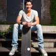 Urban asian man with skateboard sitting on stairs. Good looking. Cool guy. Wearing grey shirt and jeans. Old neglected building in the background. — Стоковая фотография