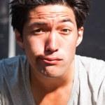 Urban asian man making funny face. Good looking. Cool guy. Wearing grey shirt. — Stock Photo #11950291