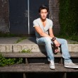 Urban asian man sitting on stairs. Good looking. Cool guy. Wearing grey shirt and jeans. Old neglected building in the background. — Zdjęcie stockowe