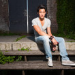 Urban asian man sitting on stairs. Good looking. Cool guy. Wearing grey shirt and jeans. Old neglected building in the background. — Foto Stock