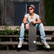 Urban asian man with hat, red sunglasses and skateboard sitting on stairs. Good looking. Cool guy. Wearing grey shirt and jeans. Old neglected building in the background. — Stock Photo