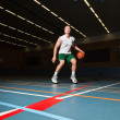 Tough healthy young man playing basketball in gym indoor. Wearing white shirt and green shorts. — Stock Photo