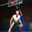 Tough healthy young man playing basketball in gym indoor. Wearing white shirt and green shorts. — Stock Photo #11955811