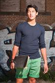 Sosteniendo un patín urbano asiatico. guapo. buen tipo. vistiendo camisa azul oscura y shorts verdes. parado frente a pared de ladrillo con graffiti. — Foto de Stock