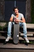 Urbano homem asiático com skate, sentado nas escadas. boa aparência. cara legal. vestindo jeans e camisa cinza. edifício em segundo plano antigo negligenciados. — Foto Stock