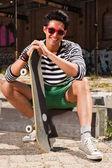 Urbano homem asiático com óculos de sol vermelhos e skate sentado na rua. boa aparência. cara legal. vestindo blusa listrada branca azul e calças verdes. edifício em segundo plano antigo negligenciados. — Foto Stock