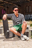 Urban asian man with red sunglasses and skateboard sitting on street. Good looking. Cool guy. Wearing blue white striped sweater and green shorts. Old neglected building in the background. — Foto Stock