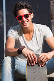 Urban asian man with red sunglasses and skateboard sitting on stairs. Good looking. Cool guy. Wearing grey shirt and jeans. — Stock Photo