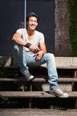 Urbano homem asiático sentado nas escadas. boa aparência. cara legal. vestindo jeans e camisa cinza. edifício em segundo plano antigo negligenciados. — Foto Stock