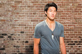 Urban asian man. Good looking. Cool guy. Wearing grey shirt. Standing in front of brick wall. — Stock Photo