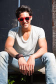 Urban asian man with red sunglasses sitting on stairs. Good looking. Cool guy. Wearing grey shirt and jeans. Old neglected building in the background. — Foto Stock