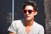 Urbano homem asiático com óculos de sol vermelhos. boa aparência. cara legal. vestindo jeans e camisa cinza. edifício em segundo plano antigo negligenciados. — Foto Stock