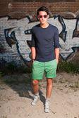 Hombre asiático urbano con gafas de sol rojos. guapo. buen tipo. vistiendo camisa azul oscura y shorts verdes. parado frente a pared de ladrillo con graffiti. — Foto de Stock