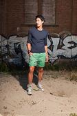 Hombre asiático urbano. guapo. buen tipo. vistiendo camisa azul oscura y shorts verdes. parado frente a pared de ladrillo con graffiti. — Foto de Stock
