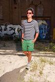 Hombre asiático urbano con gafas de sol rojos. guapo. buen tipo. usando suéter azul de rayas blanca y shorts verdes. frente a la pared con graffiti. — Foto de Stock