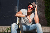 Urban asian man with hat, red sunglasses and skateboard sitting on stairs. Good looking. Cool guy. Wearing grey shirt and jeans. Old neglected building in the background. — Foto Stock