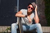 Urbano homem asiático com chapéu, óculos de sol vermelhos e skate sentado nas escadas. boa aparência. cara legal. vestindo jeans e camisa cinza. edifício em segundo plano antigo negligenciados. — Foto Stock