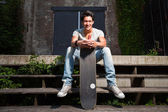 Urban asian man with skateboard sitting on stairs. Good looking. Cool guy. Wearing grey shirt and jeans. Old neglected building in the background. — Stock Photo