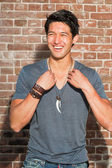 Smiling urban asian man. Good looking. Cool guy. Wearing grey shirt. Standing in front of brick wall. — Stock Photo