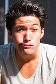 Urban asian man making funny face. Good looking. Cool guy. Wearing grey shirt. — Stock Photo