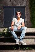 Urbano homem asiático com óculos de sol vermelhos, sentado nas escadas. boa aparência. cara legal. vestindo jeans e camisa cinza. edifício em segundo plano antigo negligenciados. — Foto Stock