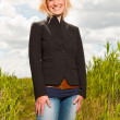 Happy pretty young blond woman enjoying nature. Field with high grass. Blue cloudy sky. Black jacket. — Stock Photo #11989247