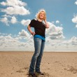 Happy pretty blond woman on the beach. Enjoying nature. Blue cloudy sky. Wearing black sweater. — Stock Photo
