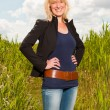 Happy pretty young blond woman enjoying nature. Field with high grass. Blue cloudy sky. Black jacket. — Stock Photo