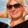 Happy pretty blond woman on the beach. Enjoying nature. Blue cloudy sky. Wearing black sweater and sunglasses. — Stock Photo #11989406