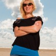 Happy pretty blond woman on the beach. Enjoying nature. Blue cloudy sky. Wearing black sweater and sunglasses. — Stock Photo